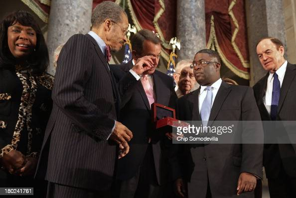 Speaker of the House John Boehner wipes away a tear while presenting the Congressional Gold Medal to Dr Lawrence Pijeaux of the Birmingham Civil...