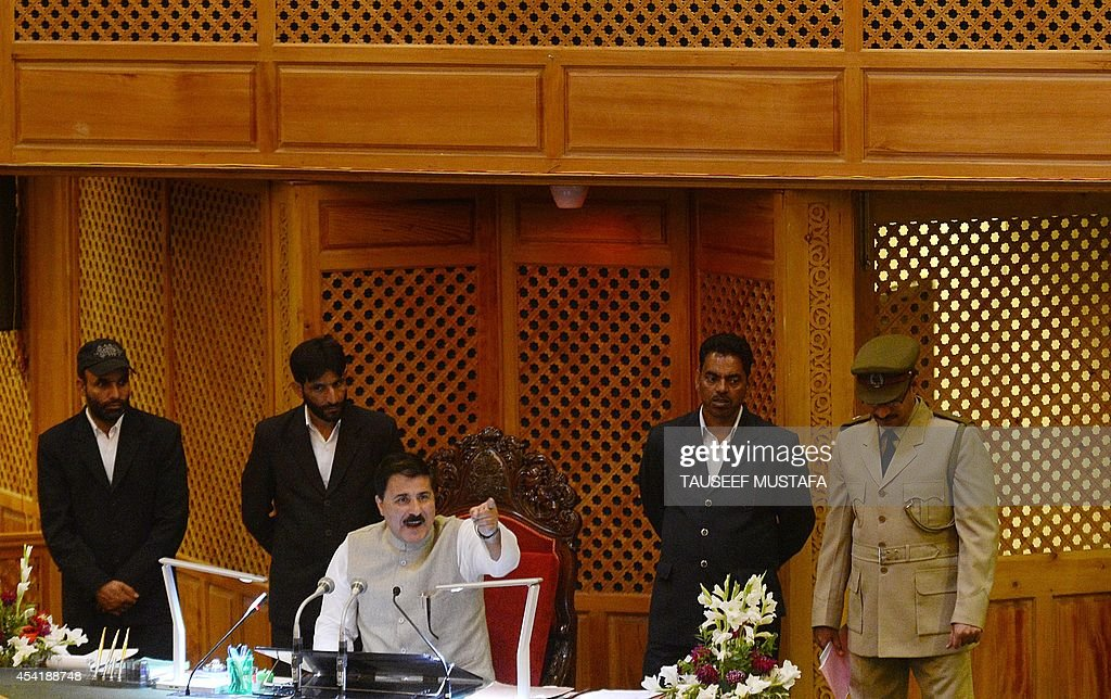 Speaker of the House Mubarak Gul (C) restores order after members of Indian-administered Kashmir's main opposition Peoples Democratic Party (PDP) shouted slogans inside the state legislative assembly in Srinagar on August 26, 2014. The Peoples Democratic Party (PDP) has demanded a discussion regarding criminal cases registered against some 6,000 youths in the Kashmir Valley, accused to stone-throwing, arguing those with cases registered against them are unable to seek government jobs or apply for passports. AFP PHOTO/Tauseef MUSTAFA