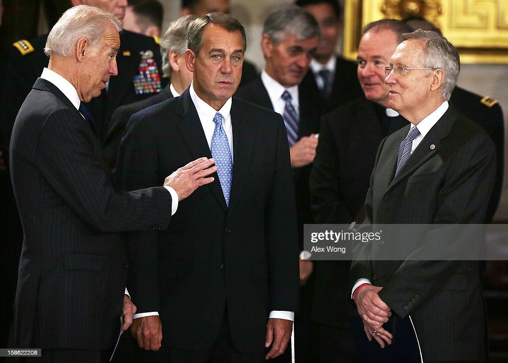 U.S. Speaker of the House Rep. John Boehner (R-OH) (C) listens to Vice President <a gi-track='captionPersonalityLinkClicked' href=/galleries/search?phrase=Joseph+Biden&family=editorial&specificpeople=206897 ng-click='$event.stopPropagation()'>Joseph Biden</a> (L) as Senate Majority Leader Sen. <a gi-track='captionPersonalityLinkClicked' href=/galleries/search?phrase=Harry+Reid+-+Pol%C3%ADtico&family=editorial&specificpeople=203136 ng-click='$event.stopPropagation()'>Harry Reid</a> (D-NV) looks on as Sen. Daniel Inouye (D-HI) lies in state in the Rotunda of the U.S. Capitol during a service December 20, 2012 on Capitol Hill in Washington, DC. A public funeral service will be held at the Washington National Cathedral tomorrow for Senator Inouye, a World War II veteran and the second-longest serving senator in history, who died at the age of 88 on December 17 at Walter Reed National Military Medical Center in Bethesda, Maryland, where he had been hospitalized since early December. His remains will be returned and laid to rest in his home state.