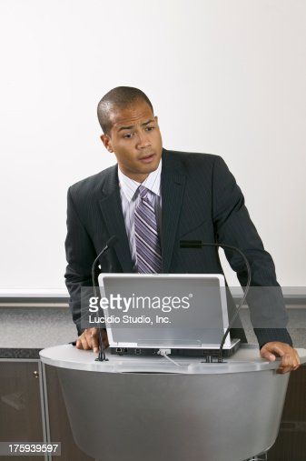 Speaker standing at a podium : Stock Photo