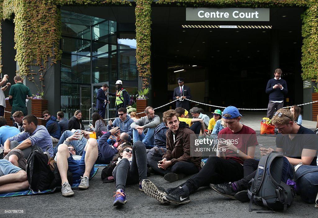 Specatators wait for the start of play on the fourth day of the 2016 Wimbledon Championships at The All England Lawn Tennis Club in Wimbledon, southwest London, on June 30, 2016. / AFP / JUSTIN