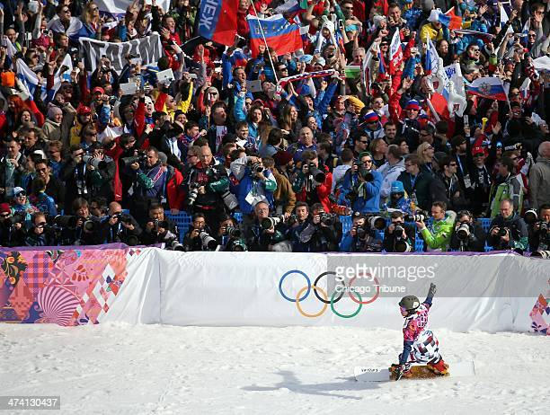 Specators cheer as Vic Wild of Russia finishes his gold medal run in men's snowboard parallel slalom at the Rosa Khutor Extreme Park during the...