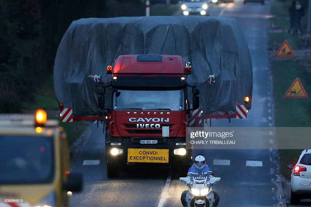 A special convoy transporting a lid that is to be installed on the vessel of the nuclear reactor EPR, currently under construction at Flamanville, drives on a highway in Marseille-en-Beauvaisis, northern France on February 10, 2016. The convoy transporting the lid of110 tons that measures 5,5 meters in diameter left the Areva plant on Chalon-sur-Saône, eastern France, on the morning of February 8 and is expected to arrive at its destination on February 11 or 12, Areva and EDF confirmed. AFP PHOTO / CHARLY TRIBALLEAU / AFP / CHARLY TRIBALLEAU