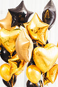 Special days decoration. Fancy party essential. Golden and black round, heart, star shaped balloons on white background.