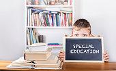 Special education. Boy holding blackboard