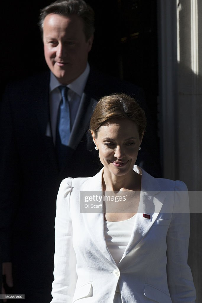 UN Special Envoy and actress Angelina Jolie prepares to pose for a photograph with British Prime Minster David Cameron outside Number 10 Downing Street after having attended the Global Summit To End Sexual Violence In Conflict at the ExCeL centre on June 10, 2014 in London, England. The four-day conference on sexual violence in war is hosted by Foreign Secretary William Hague and UN Special Envoy and actress Angelina Jolie.