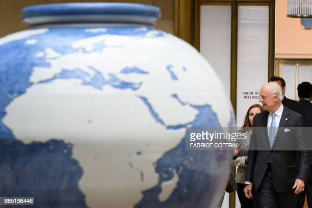 UN Special Envoy for Syria Staffan de Mistura walks behind a giant vase prior to a meeting with members of Syria's main opposition High Negotiations...