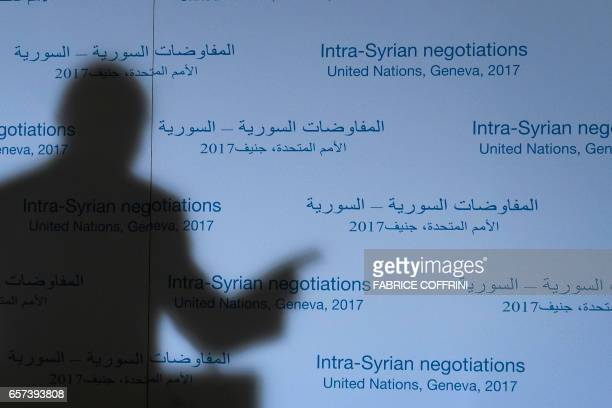 UN Special Envoy for Syria Staffan de Mistura's shadow is cast on a backdrop during a press conference following a meetings on Syria peace talks on...