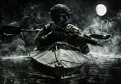 Two special forces operators with night vision goggles paddling in the army kayak in the jungle. Cloudy night, full moon, damp