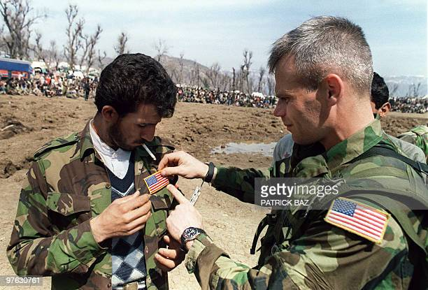 Special Forces Sgt sticks 21 April 1991 near Cirze on IraqTurkey border a US flag on the jacket of an Iraqi soldier who fled from the Iraqi army in...