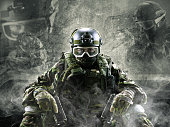 A special forces soldier sits on a gray background with a smoke effect. Holds a gun in his hands and looks into the camera.