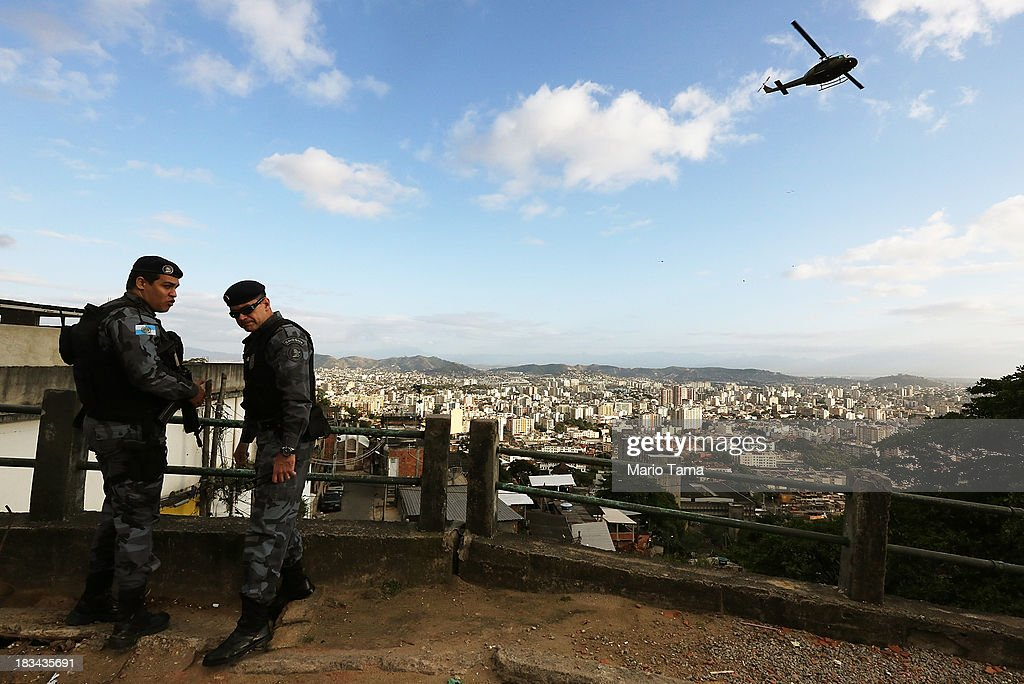 Special forces soldiers stand by as a military helicopter flies overhead during a 'pacification' operation in the favela complex of Lins de Vasconcelos, in the North Zone, on October 6, 2013 in Rio de Janeiro, Brazil. The favela complex, or shanty town, was previously controlled by drug traffickers and will now be occupied by the city's 35th UPP or 'Police Pacification Unit'. The favela pacifications are occurring amid Rio de Janeiro's efforts to improve security ahead of the 2014 FIFA World Cup and 2016 Olympic Games.