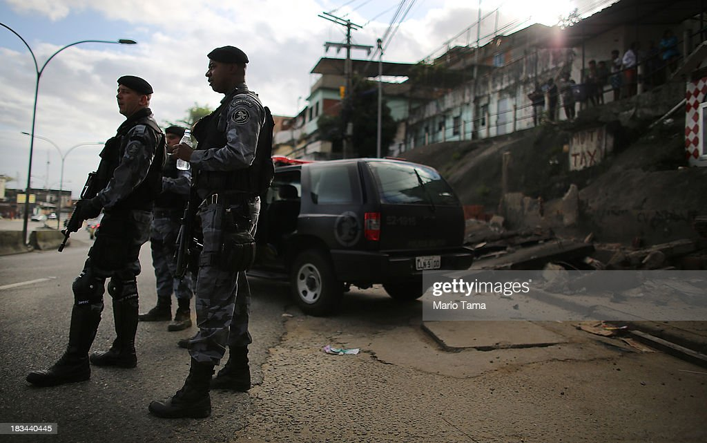 Special forces soldiers stand by during a 'pacification' operation in the favela complex of Lins de Vasconcelos, in the North Zone, on October 6, 2013 in Rio de Janeiro, Brazil. The favela complex, or shanty town, was previously controlled by drug traffickers and will now be occupied by the city's 35th UPP or 'Police Pacification Unit'. The favela pacifications are occurring amid Rio de Janeiro's efforts to improve security ahead of the 2014 FIFA World Cup and 2016 Olympic Games.
