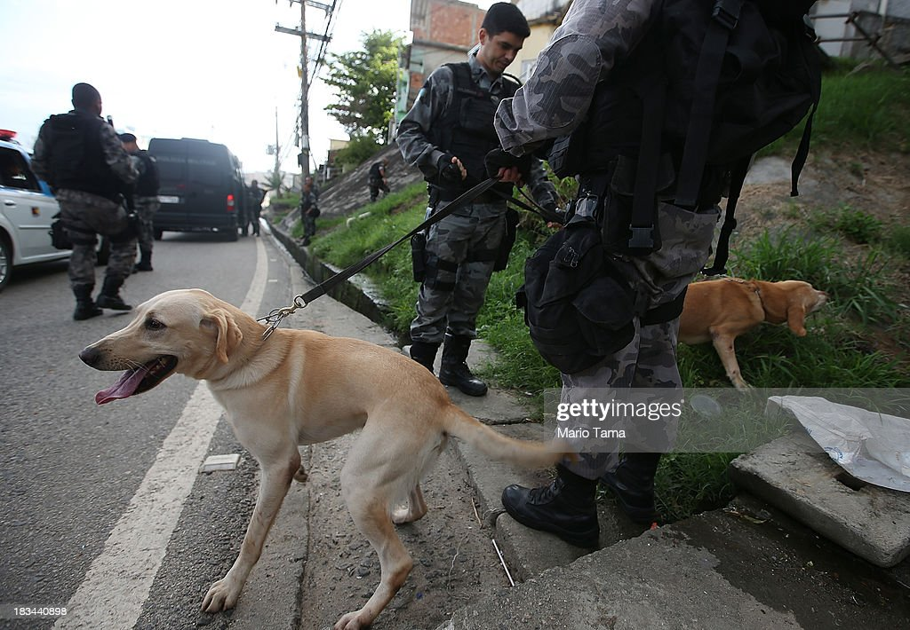 Special forces soldiers standy by with dogs trained to sniff for drugs and weapons during a 'pacification' operation in the favela complex of Lins de Vasconcelos, in the North Zone, on October 6, 2013 in Rio de Janeiro, Brazil. The favela complex, or shanty town, was previously controlled by drug traffickers and will now be occupied by the city's 35th UPP or 'Police Pacification Unit'. The favela pacifications are occurring amid Rio de Janeiro's efforts to improve security ahead of the 2014 FIFA World Cup and 2016 Olympic Games.