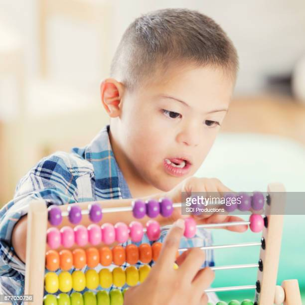 Special needs boy counts beads on abacus