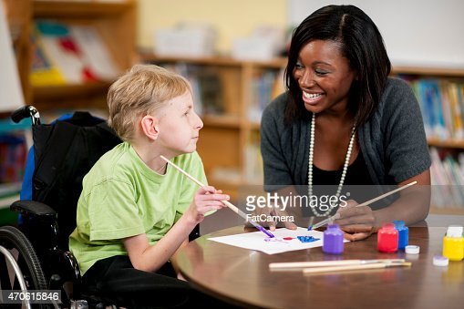 Special Needs Boy Painting with Teacher