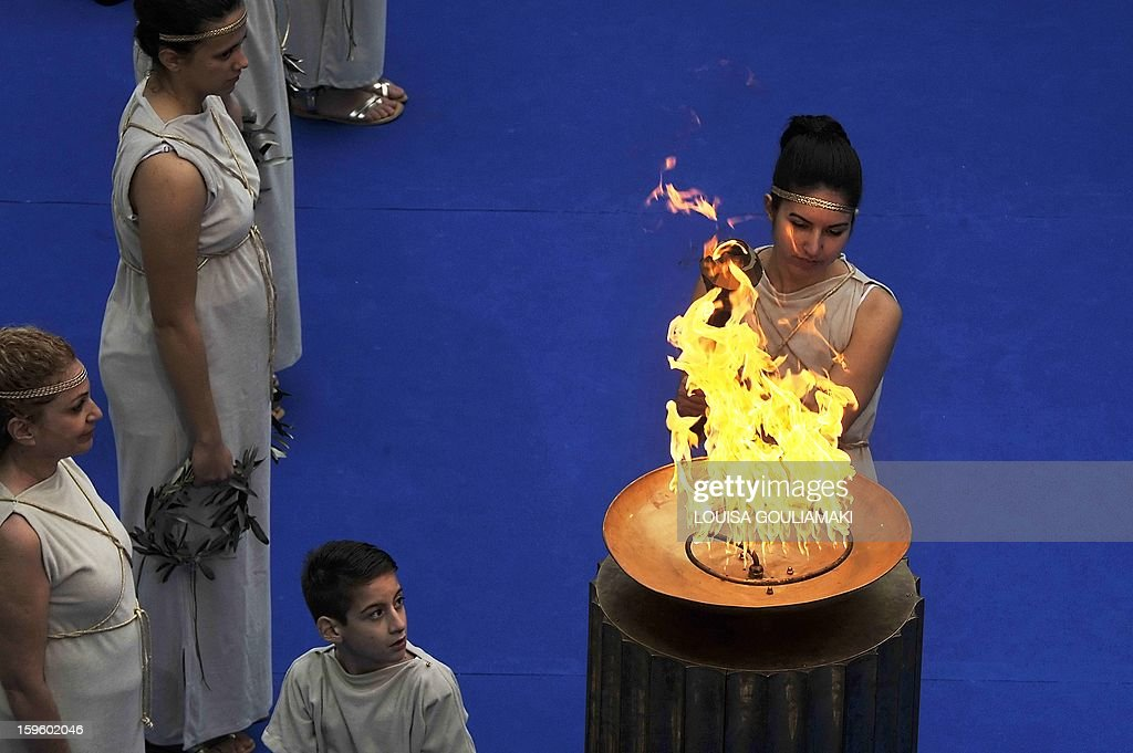 Special Olympic gymnastics athletes, in the role of ancient Greek priestesses, lit the cauldron with the Olympic torch during the lighting of the 'Flame of Hope' for the 2013 Pyeong Chang World Winter Games at the Zappion megaron in Athens on January 17, 2012. AFP PHOTO/ Louisa Gouliamaki