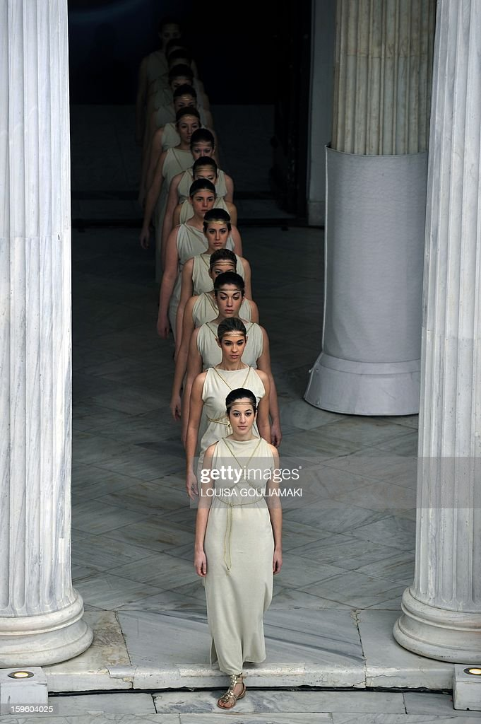 Special Olympic gymnastics athletes, in the role of ancient Greek priestesses, perform during the lighting of the 'Flame of Hope' for the 2013 Pyeong Chang World Winter Games at the Zappion megaron in Athens on January 17, 2012. AFP PHOTO/ Louisa Gouliamaki