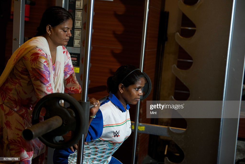 Special Olympics Gold and Bronze medalist Phoolan Devi with her powerlifting coach and house auntie Seema at the gym on August 14, 2015 in New Delhi, India. Phoolan Devi, 17 has an IQ of 46. She won four medals in the power-lifting contest one gold and three bronze at the games held in Los Angeles from 25 July-2 August.
