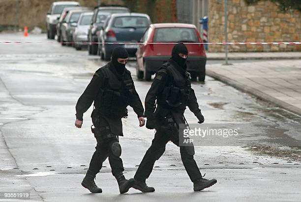 Special police members walk by the entrance of the German School in the northern Greek city of Thessaloniki on December 2 2009 during the hostage...