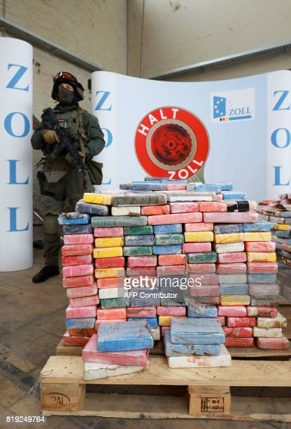 A special unit customs officer stands next to a pallet of cocaine packets during a press conference on July 20 2017 in Hamburg 38 tons of cocaine...
