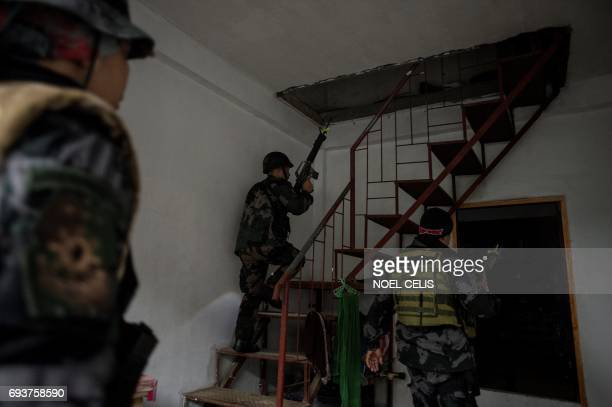 A Special Weapons and Tactics operative searches a house after receiving information that more than a dozen escaped prisoners freed from jail by...