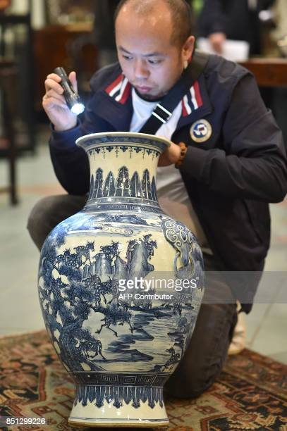 A specialist in Chinese artifacts uses a torch as he examines a large balustershaped vase decorated with blue deer under pines in Toulouse on...