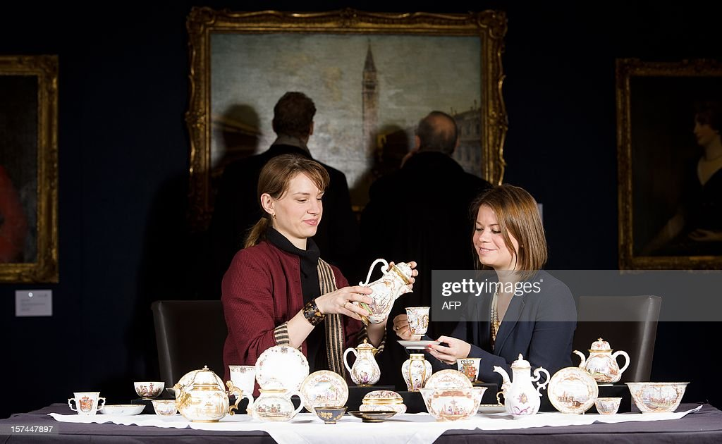 Specialist in European Ceramics Nette Megens (L) poses with a rare early Meissen coffee pot while sitting with Bonhams staff member Coralie Whittall during a photocall on December 3, 2012 to promote the forthcoming Marouf Collection sale of 18th century Meissen porcelain. The sale will be held on December 5, 2012 at Bonham on New Bond Street, London. AFP PHOTO/Leon Neal