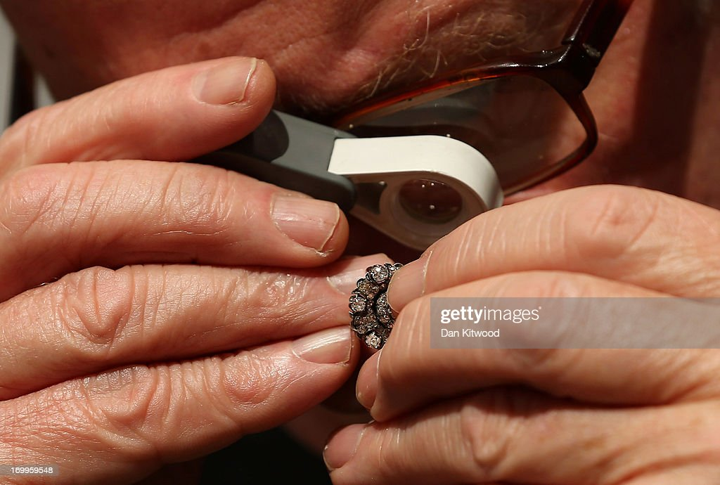A specialist inspects a pair of antique Russian earrings ahead of the Olympia 'International Fine Art and Antiques Fair' at Olympia Exhibition Centre on June 5, 2013 in London, England. The 41st Olympia Arts and Antiques fair hosts 180 dealers selling items of 20th century design, ceramics, carpets, art deco, 18th and 19th century English furniture, modern British art and tribal art amongst other things. It will open to the public tomorrow until 16 June, 2013.