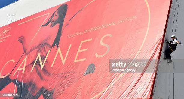 A specialist installs 70th Cannes Film Festival poster at the Palais des Festival where the 70th Cannes Film Festival films screening building in...