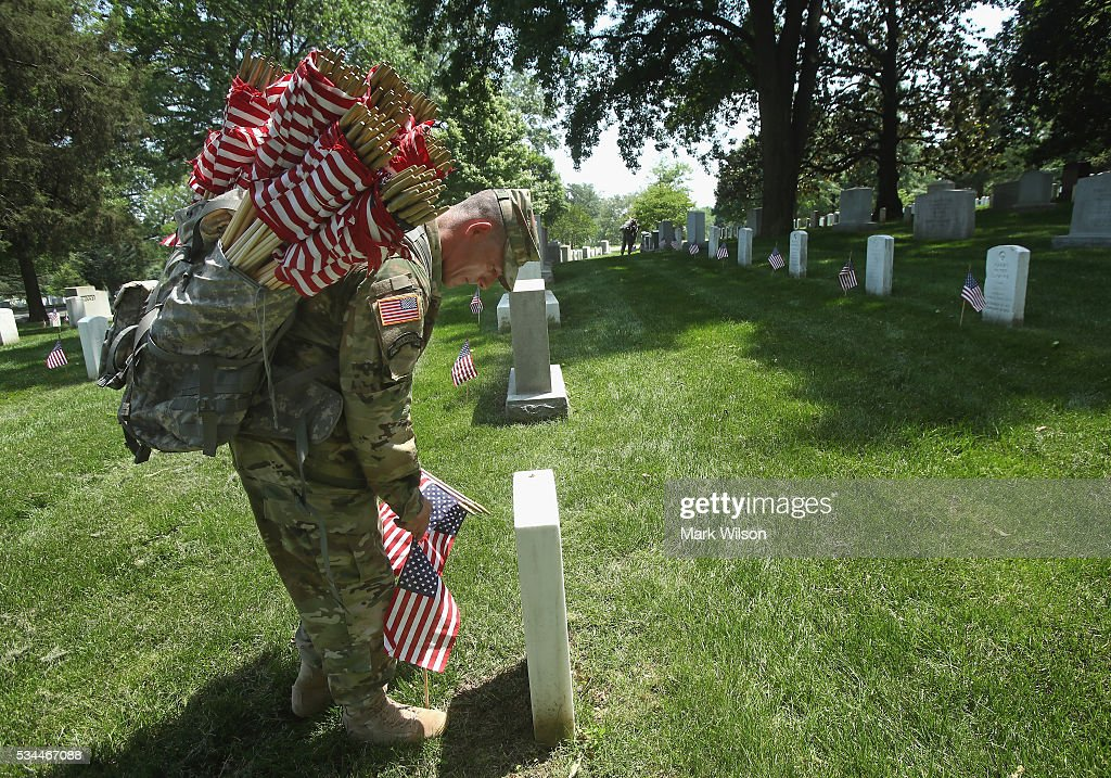 Specialist Jose Barreiro, of the 3rd U.S. Infantry Regiment, 'The Old Guard,' places a flag at a grave site during the 'Flags-In' ceremony May 26, 2016 at Arlington National Cemetery in Arlington, Virginia. A small American flag was placed one foot in front of more than 220,000 graves in the cemetery to mark Memorial Day.