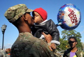 Specialist Marqes Turpin of the 273rd Military Police Company of DC Army National Guard kisses his twoyearold son Josiah Turpin as his sister Nikilae...