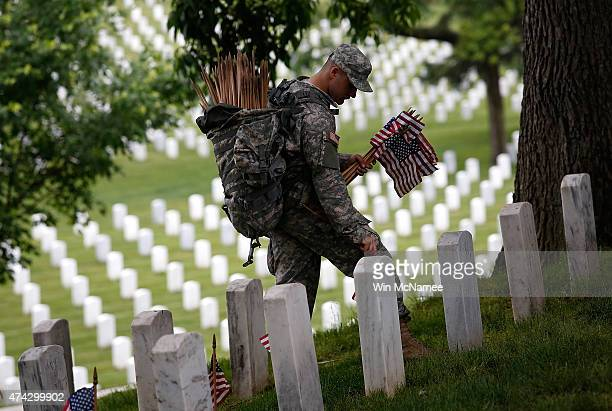 Specialist Michael Escobar of the 3rd US Infantry Regiment places American flags at the graves of US soldiers buried at Arlington National Cemetery...