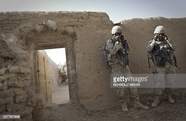 US specialist Zachary Oles and Sergeant Jesse Frederick from 595th Sapper Company 2nd Engineers Battalion protect their ears while blowing up a wall...