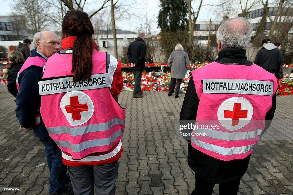 Specially trained members of the Red Cross talk to each other as mourners visit outside the local high school on March 14 2009 in Winnenden Germany...