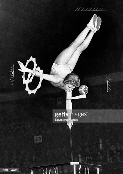 Spectacle d'acrobaties où une femme fait le poirier en équilibre sur un poteau sur une main l'autre tenant des cerceaux et dans la bouche elle porte...