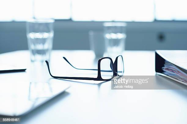 Spectacles and digital tablet on conference table