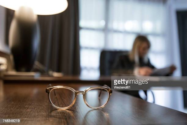Spectacles on desk with businesswoman checking documents in the background