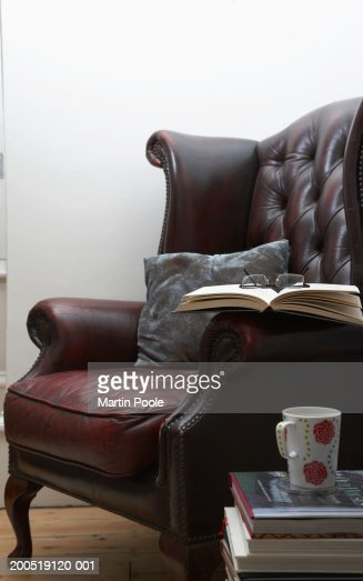 Spectacles placed on book resting on armchair : Stock Photo