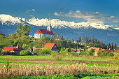 Amazing spring countryside landscape with church of Mandra and high snowy Fagaras mountains in background, Brasov region, Transylvania, Romania, Europe