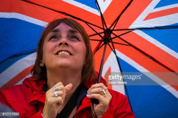 A spectator attempts to keep dry as they watch action on the screen on day eight of the Wimbledon Lawn Tennis Championships at the All England Lawn...