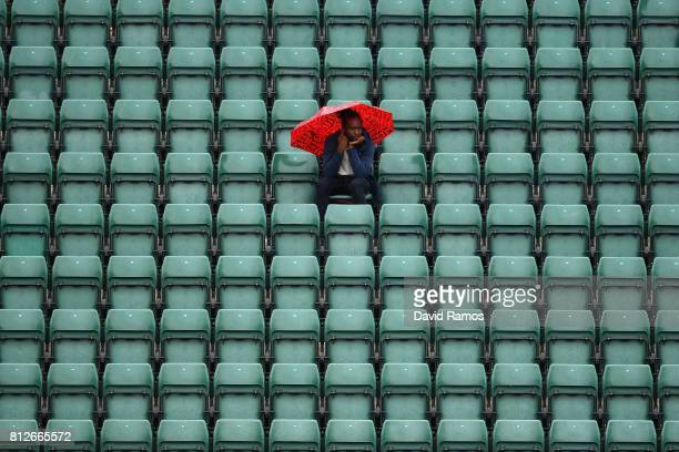 A spectator attempts to keep dry on court one as play is suspended on day eight of the Wimbledon Lawn Tennis Championships at the All England Lawn...