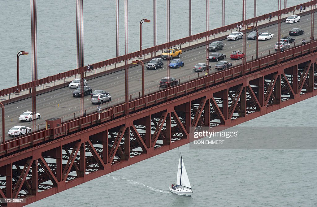 A spectator boat sails under the Golden gate Bridge in San Francisco Harbor during the America's Cup in San Francisco, California on July, 14, 2013. AFP PHOTO/Don Emmert