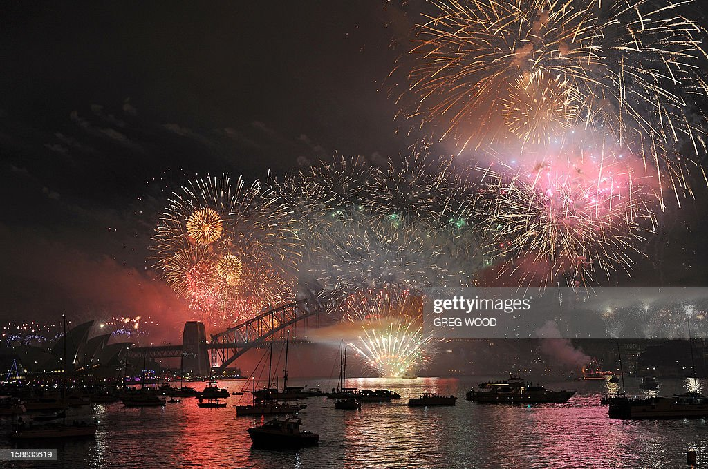 Spectator boats in Sydney Harbour (below) look on as New Year's Eve fireworks erupt over the Sydney Harbour Bridge on January 1, 2013. Sydney kicked off a wave of dazzling firework displays welcoming in 2013, from Dubai to Moscow and London, with long-isolated Yangon joining the global pyrotechnics for the first time. AFP PHOTO / Greg WOOD