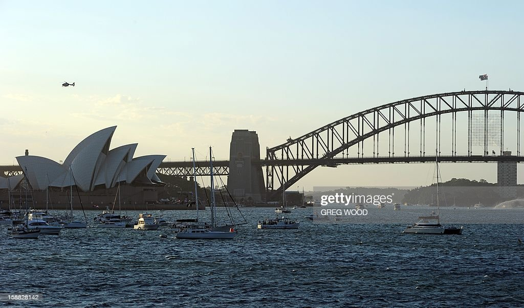 Spectator boats in Sydney Harbour (C) prepare for the New Year's Eve fireworks at midnight over the Sydney Harbour Bridge (L) and the Sydney Opera House (R) on December 31, 2012. Australia's famous harbour city will usher in the New Year with a 6.9 million USD display curated by pop icon Kylie Minogue who designed the colour scheme and soundtrack, with officials expecting more than 1.5 million people to crowd the waterfront. AFP PHOTO / MANAN VATSYAYANA