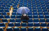 A spectator braves the weather as the rain delays day four of the 2nd Investec Test Match between England and New Zealand at Headingley on June 1...