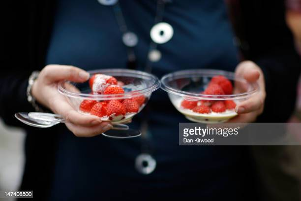 A spectator carries pots of strawberries on day five of the Wimbledon Lawn Tennis Championships at the All England Lawn Tennis and Croquet Club on...