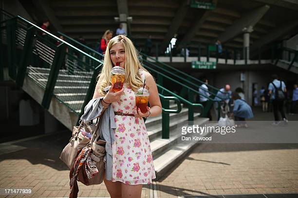 A spectator carries two plastic glasses of Pimms during day two of the Wimbledon Lawn Tennis Championships at the All England Lawn Tennis and Croquet...