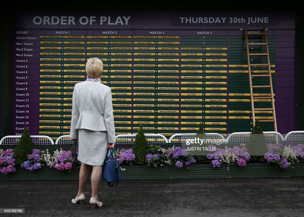 A spectator checks the order of play on the fourth day of the 2016 Wimbledon Championships at The All England Lawn Tennis Club in Wimbledon, southwest London, on June 30, 2016. / AFP / JUSTIN