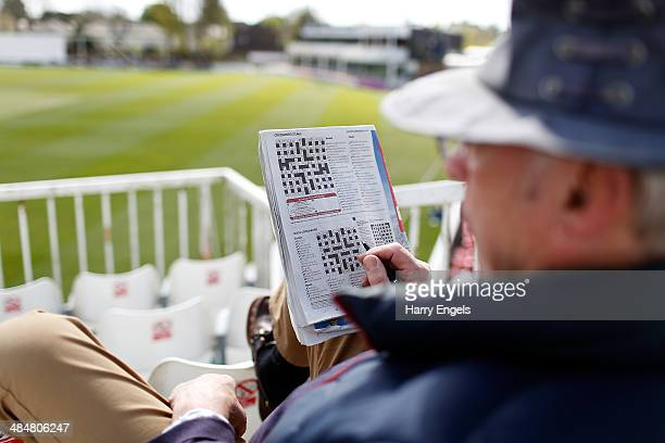 A spectator does a crossword puzzle whilst watch play on day two of the LV County Championship Division Two match between Essex and Derbyshire at the...